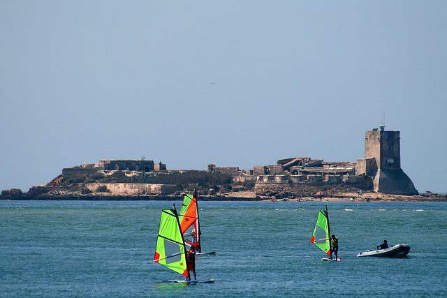 Castillo de Sancti Petri con gente haciendo Windsurf